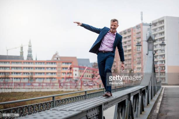 Stylish mature businessman wearing blue suit balancing on railing of bridge