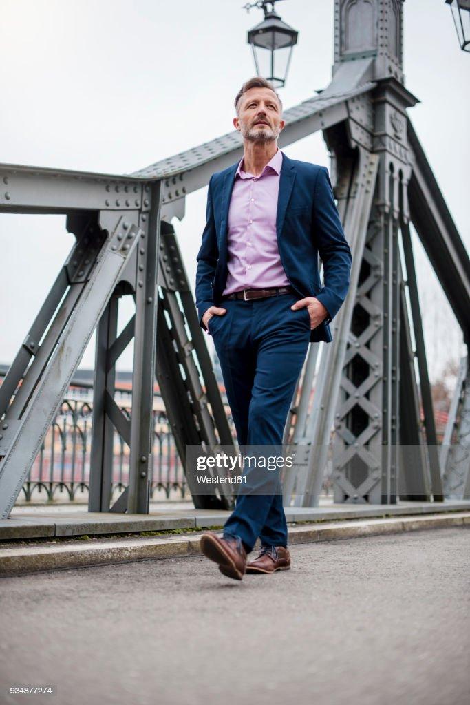 Stylish mature businessman wearing blue suit walking on bridge : Stock Photo