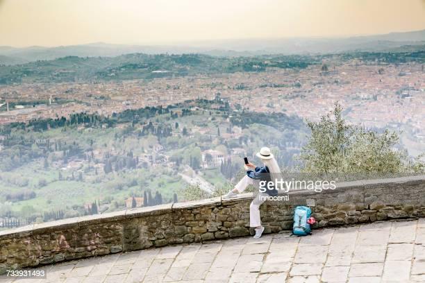 Stylish mature woman sitting on wall photographing view, Fiesole, Tuscany, Italy