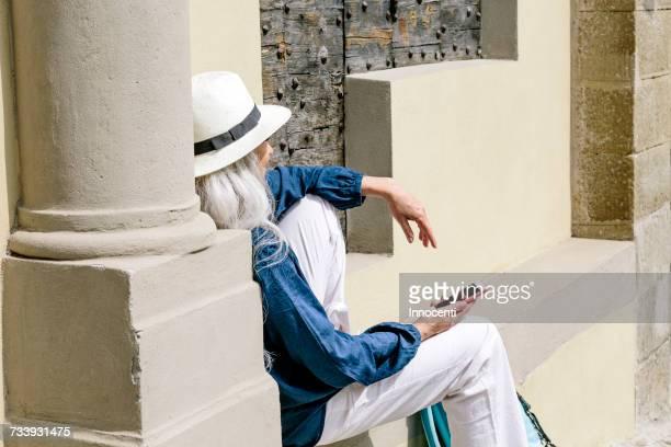 Stylish mature woman sitting outside church, Fiesole, Tuscany, Italy