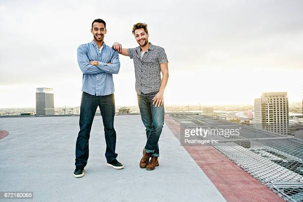 stylish men posing on urban rooftop - zwei personen stock-fotos und bilder