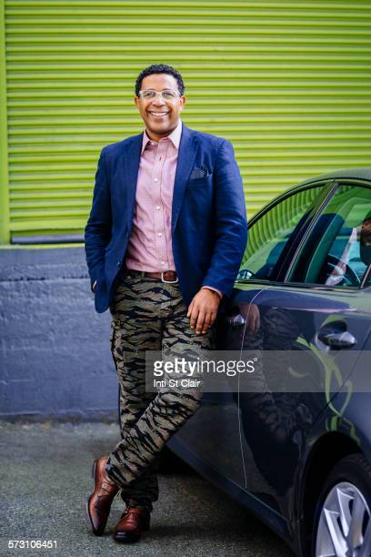 stylish mixed race businessman leaning on car - handsome native american men stock pictures, royalty-free photos & images