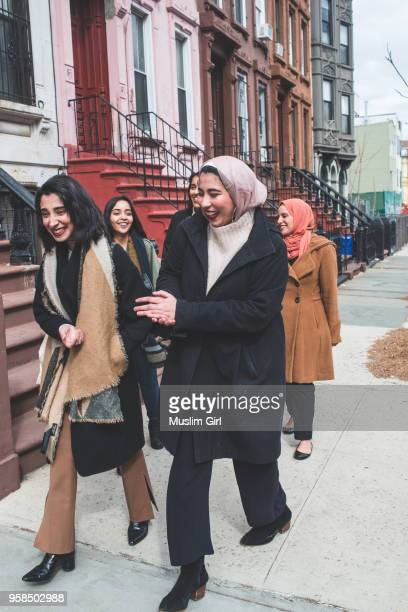 stylish muslim girls walking in a residential neighborhood - muslimgirlcollection stock pictures, royalty-free photos & images