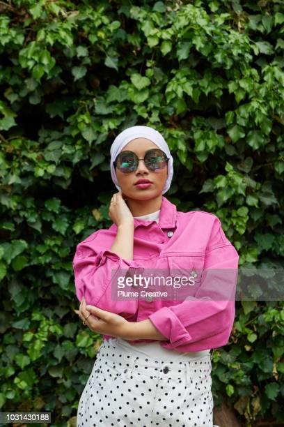 Stylish Muslim Woman standing in front of lush foliage