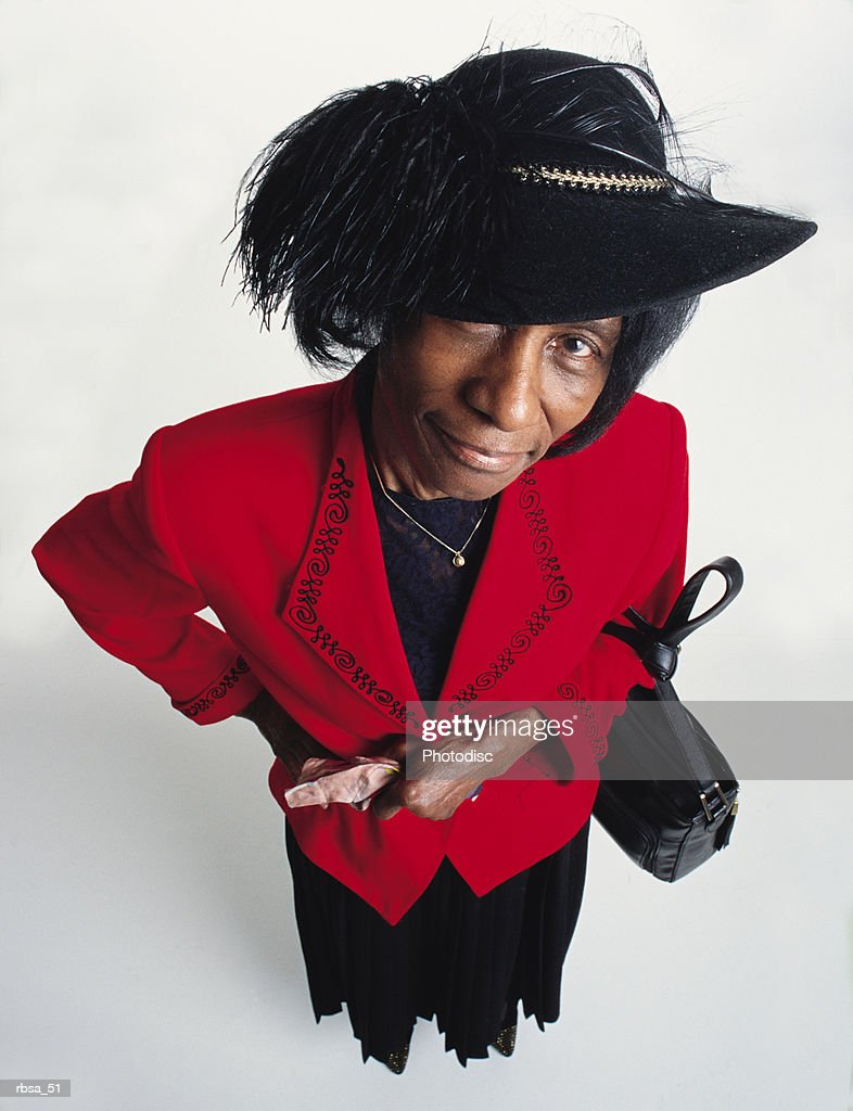 stylish old african american adult female wearing a red blazer and a dark skirt is holding gloves and has a purse over her left arm as she looks up grinning at the camera from under a felt hat with a large feather on it : Stockfoto
