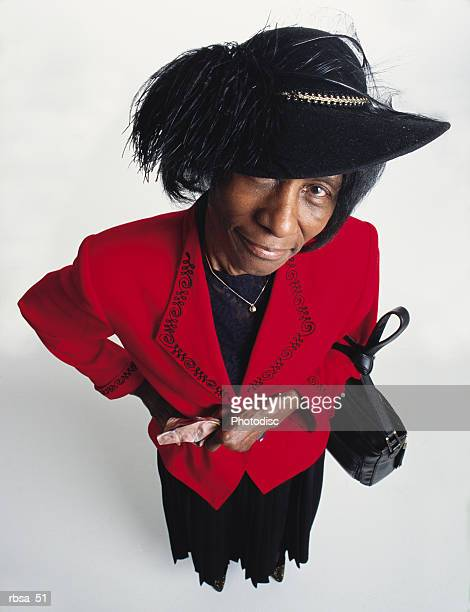 stylish old african american adult female wearing a red blazer and a dark skirt is holding gloves and has a purse over her left arm as she looks up grinning at the camera from under a felt hat with a large feather on it - 一張羅 ストックフォトと画像