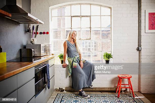 A stylish older woman sits in her kitchen window