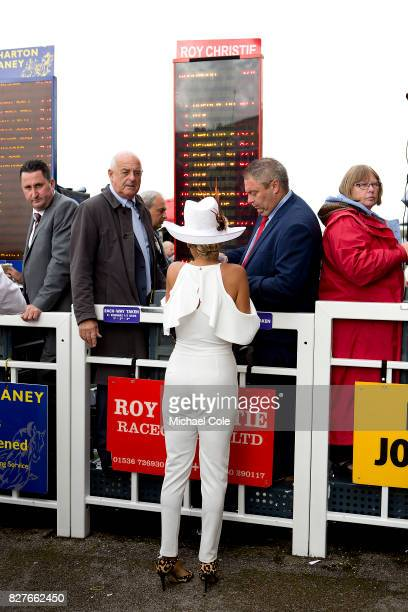 Stylish racegoer placing a bet with with a bookmaker near The Gordon Enclosure 'Ladies Day' at 'Glorious Goodwood' The Qatar Goodwood Festival at...