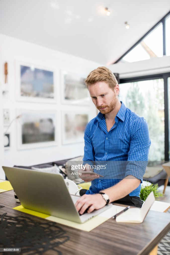 Stylish red haired man typing information that he got from laptop. Worplace, home office. : Stock Photo