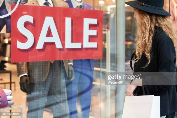 stylish red head millennial wearing a hat going shopping inside of a mall - reduction stock pictures, royalty-free photos & images