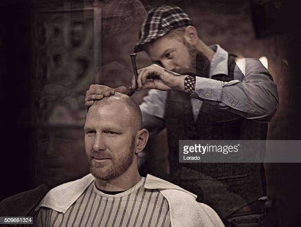 Stylish retro bearded barber shaving a bearded bald male client