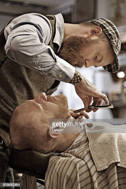 Stylish retro bearded barber with a bearded bald male client