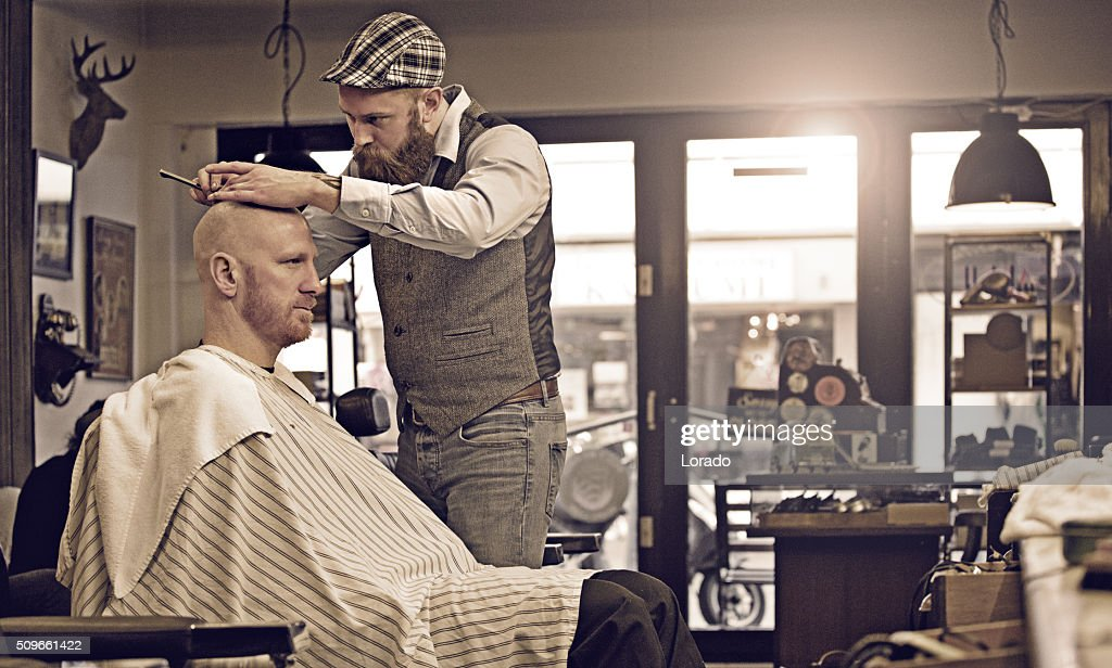 Stylish retro bearded barber with a bearded bald male client : Stock Photo