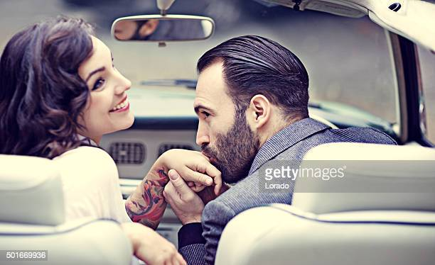 Stylish retro couple in love in a vintage car