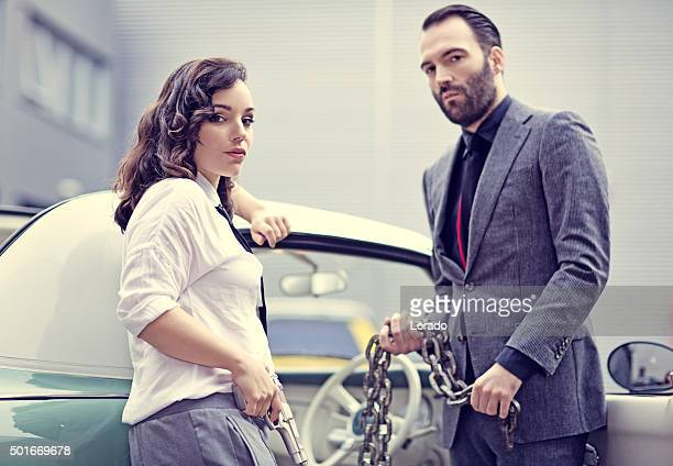 Stylish retro gangster couple standing with vintage car