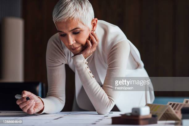 stylish senior female architect designing a plan for her latest project - design professional stock pictures, royalty-free photos & images