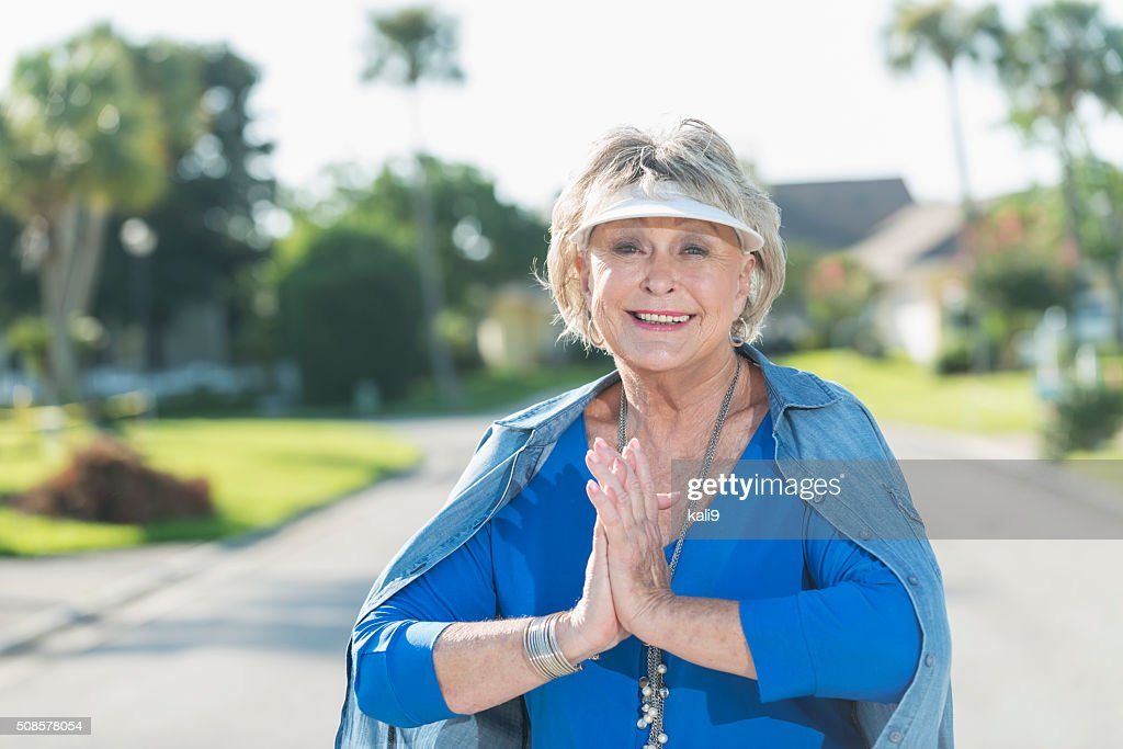 Stylish, senior woman standing outdoors on sunny day : Stock Photo