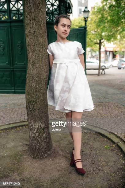 stylish teenage girl in white festive dress leaning on tree outdoors in Berlin