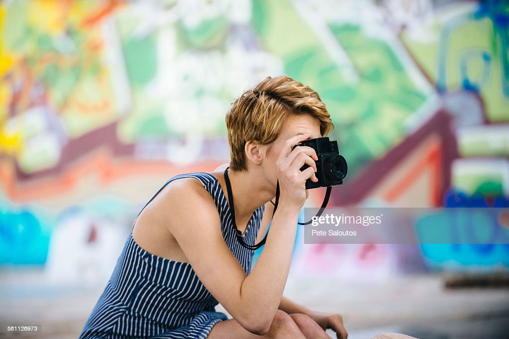 Stylish teenage girl photographing with camera in front of graffiti wall : Stockfoto