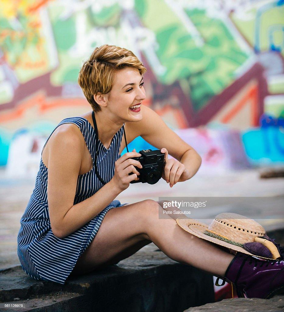 Stylish teenage girl sitting on sidewalk with camera in front of graffiti wall : Stock Photo