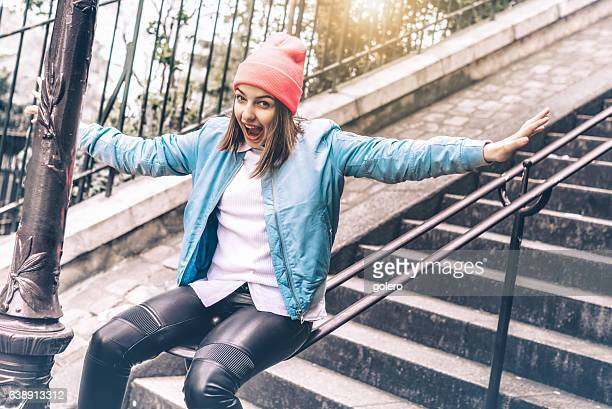 stylish teenage girl slipping down ballustrade of monmartre stairs