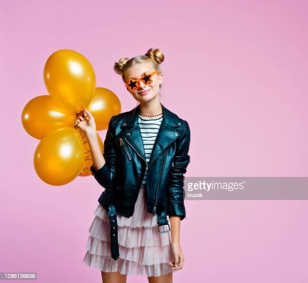 stylish teenege girl holding gold balloons - embellished jacket stock pictures, royalty-free photos & images