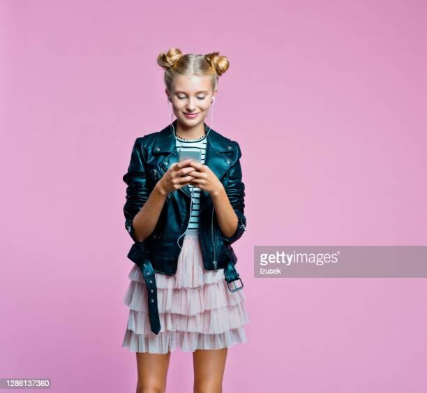 garota teenege elegante usando telefone inteligente - izusek - fotografias e filmes do acervo