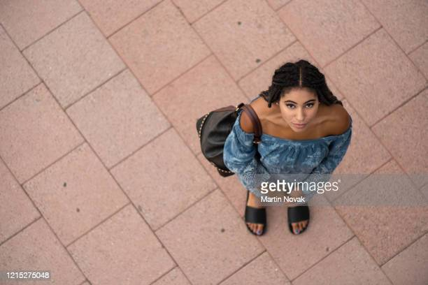 stylish traveler teenager looking above at camera - strapless stock pictures, royalty-free photos & images