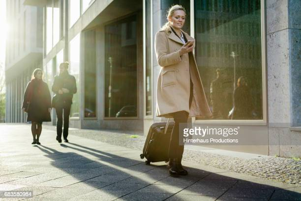 Stylish Travelling Business Woman Using Her Smartphone In The City