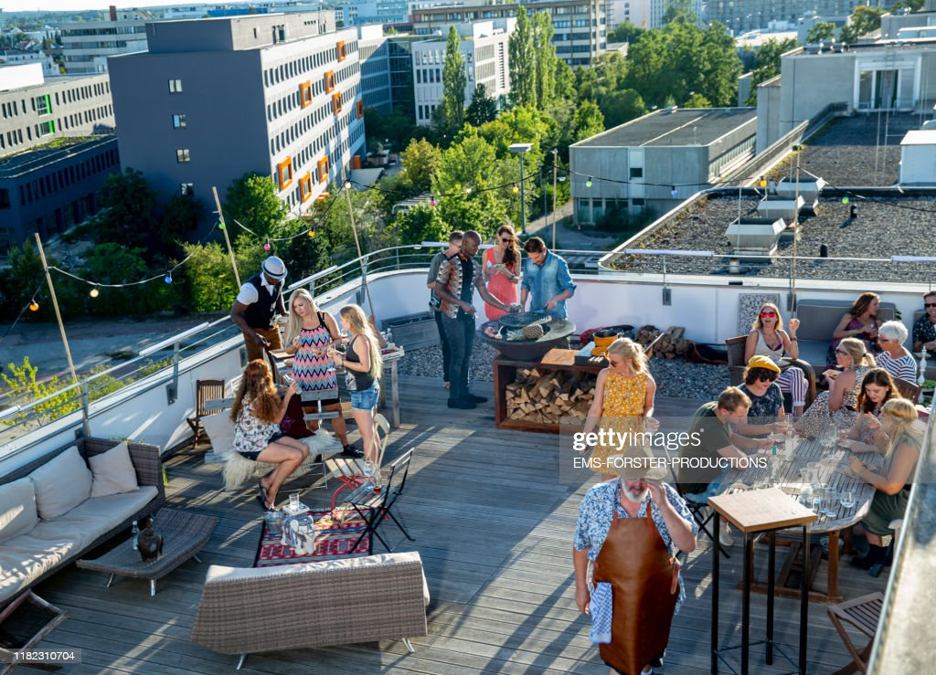 20 stylish, trendy co-workers enjoying office party grill on roof deck on sunny summer day : Foto de stock