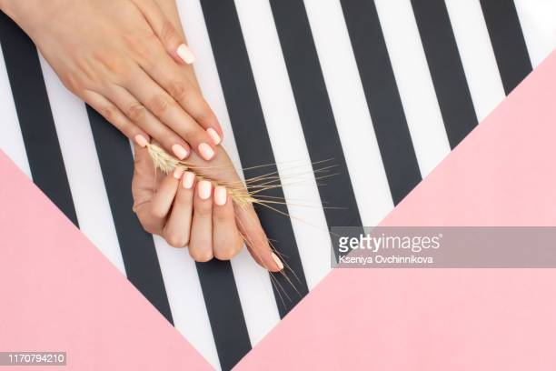 Stylish trendy female manicure. Beautiful young woman's hands on pink and blue background.