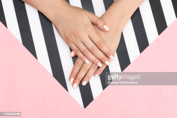 stylish trendy female white, black and blue manicure. beautiful young woman's hands on pink and white background. - nail varnish stock pictures, royalty-free photos & images