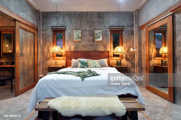 stylish tropical bedroom at night - villa photos et images de collection