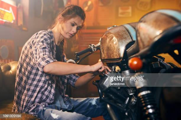 stylish vintage hobby motorcycle garage.woman at work - vintage motorcycle stock pictures, royalty-free photos & images