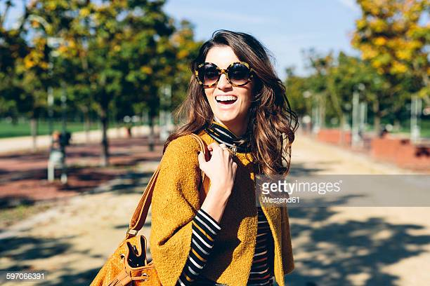 stylish woman at the park on a sunny autumn day - shoulder bag stock pictures, royalty-free photos & images