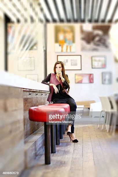 Stylish Woman Drinking Coffee at a Cafe