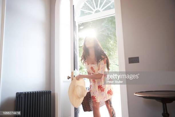 stylish woman entering hotel doorway carrying suitcase - ankunft stock-fotos und bilder