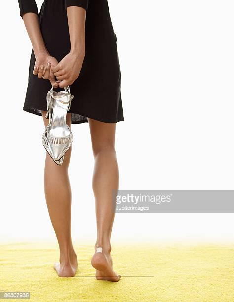 Stylish woman holding high heels