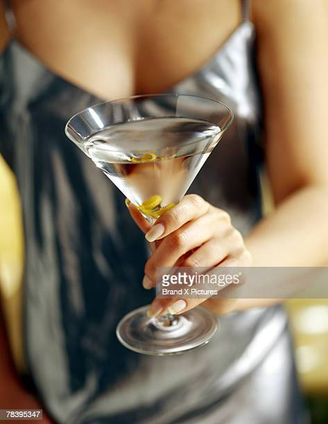 stylish woman holding martini - dirty martini stock photos and pictures