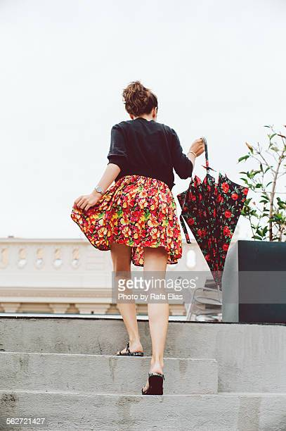 Stylish woman holding umbrella going upstairs