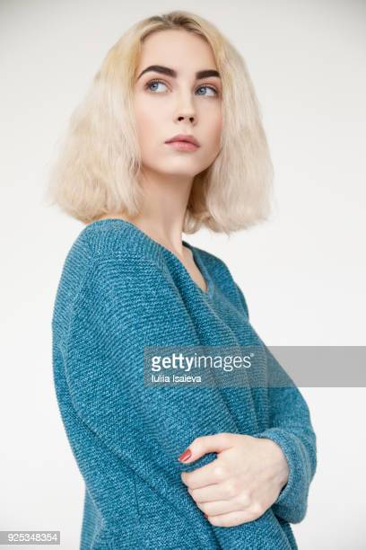 stylish woman in blue sweater in studio - cadrage aux genoux photos et images de collection