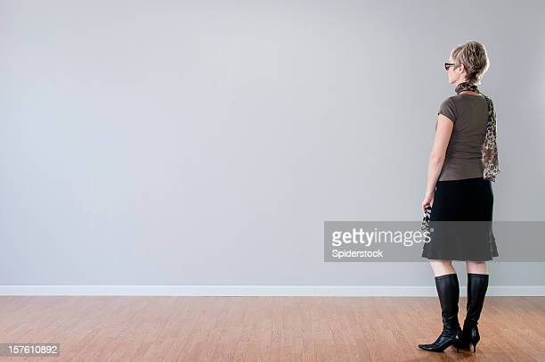 stylish woman looking at blank wall - gray skirt stock pictures, royalty-free photos & images