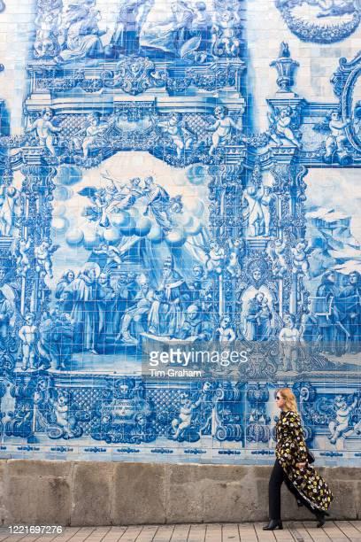 Stylish woman passes azulejos Portuguese blue and white ceramic wall tiles of Capela das Almas de Santa Catarina St Catherine's Chapel in Porto...