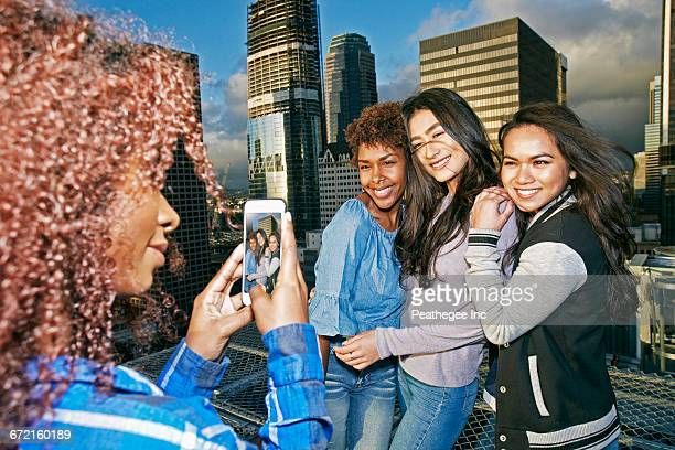 Stylish woman photographing friends on urban rooftop with cell phone