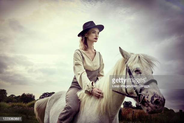 stylish woman riding horse in the countryside - editorial stock pictures, royalty-free photos & images