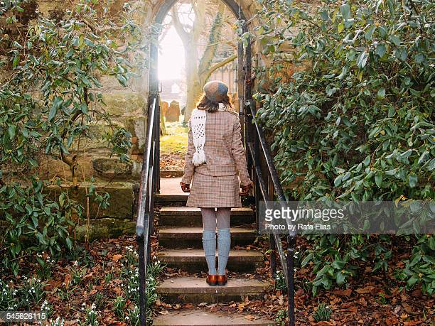 stylish woman standing at the gate of the cemetery - イギリス ウォリック ストックフォトと画像