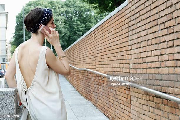 Stylish woman talking on smartphone on street, Milan, Italy