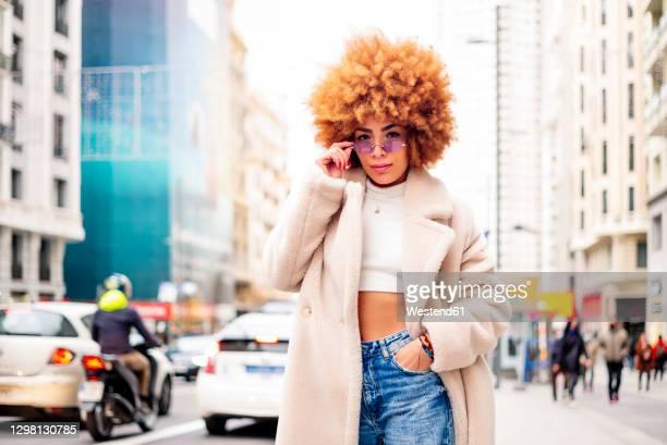 stylish woman with blond hair wearing sunglasses standing on street - kroeshaar stockfoto's en -beelden