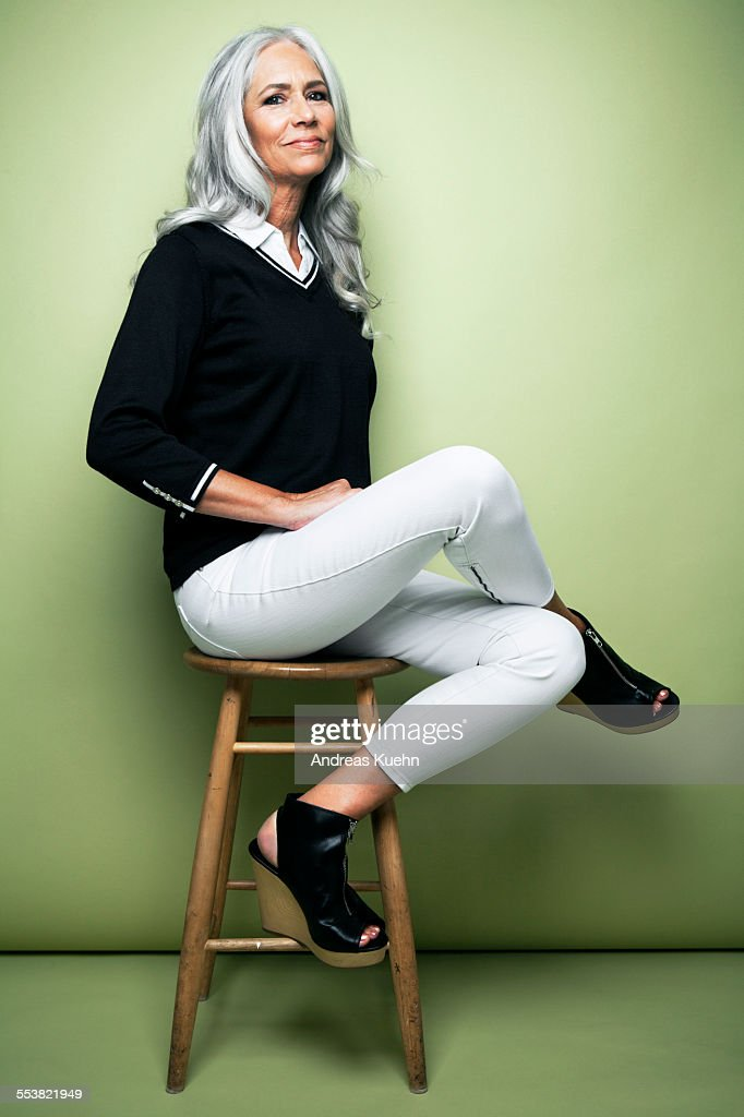 Stylish woman with grey hair sitting on a stool. : Stock Photo