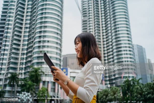 stylish young asian businesswoman using digital tablet in downtown financial district in the city - international landmark stock pictures, royalty-free photos & images